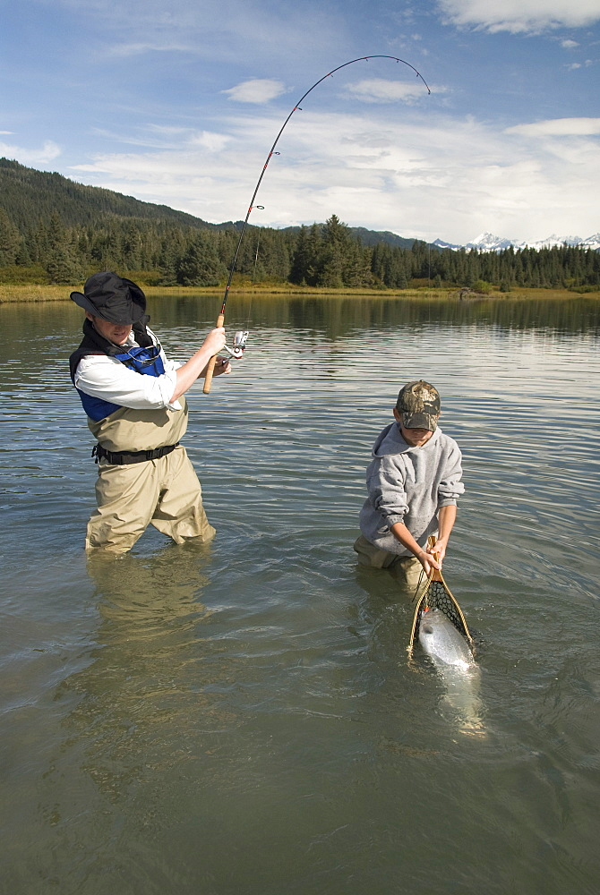 Fisherman catching a Silver (Coho) salmon (Oncorhynchus kisutch) with boy netting the fish, Coghill Lake, Alaska, United States of America, North America