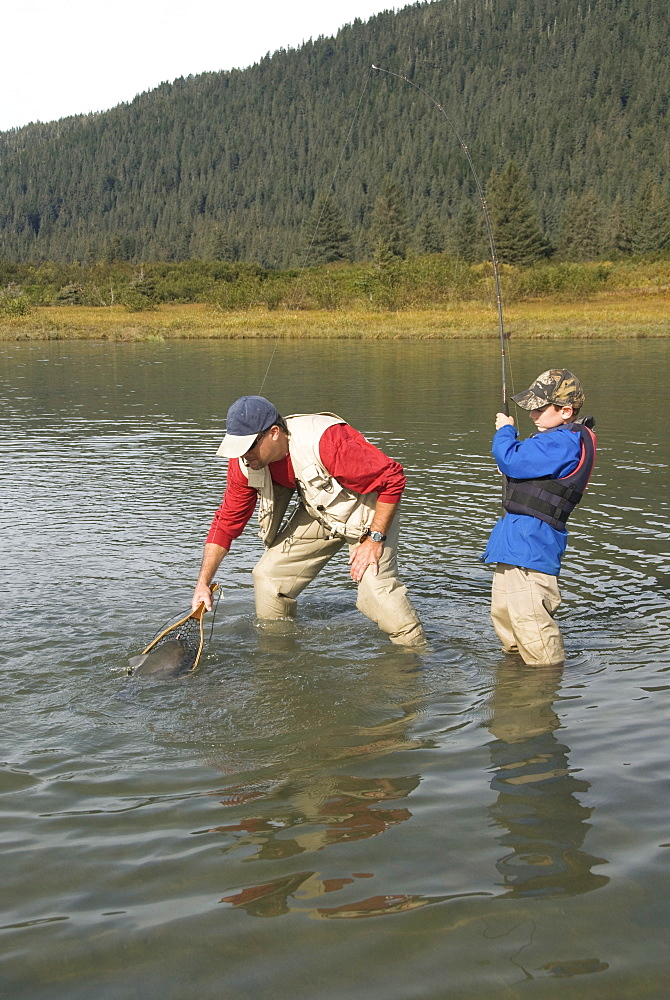 Boy catching a Silver (Coho) salmon (Oncorhynchus kisutch) with dad's help, Coghill Lake, Alaska, United States of America, North America