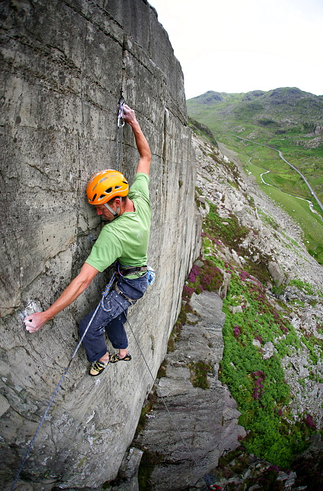 A rock climber makes a first ascent of on the cliffs above the Llanberis Pass, Snowdonia National Park, Wales, United Kingdom
