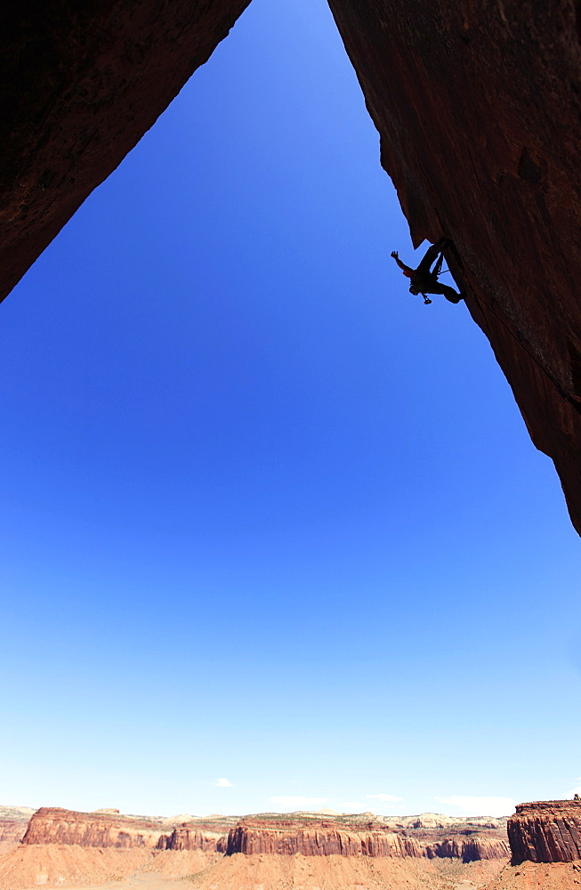 A rock climber tackles an overhanging wall on the cliffs of Indian Creek, a famous rock climbing area near Moab, south eastern Utah, United States of America, North America