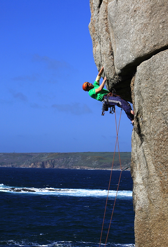 A climber tackles a difficult overhang on the cliffs near Sennen Cove, a popular rock climbing area at Lands End, Cornwall, England, United Kingdom, Europe