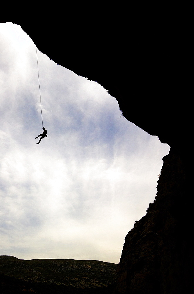 A climber is lowered from a the edge of a huge cave in the Mascun Gorge, near Rodellar, Sierra de Guara mountains, northern Spain, Europe