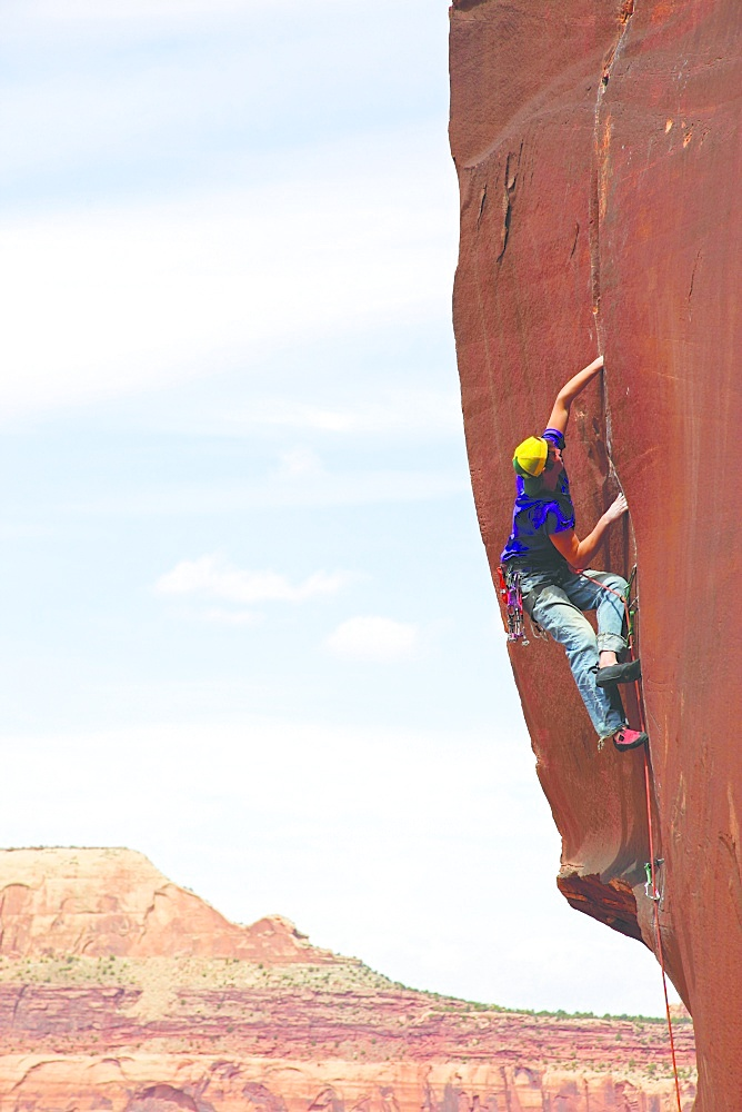 A climber scales cliffs at Indian Creek, Utah, United States of America, North America
