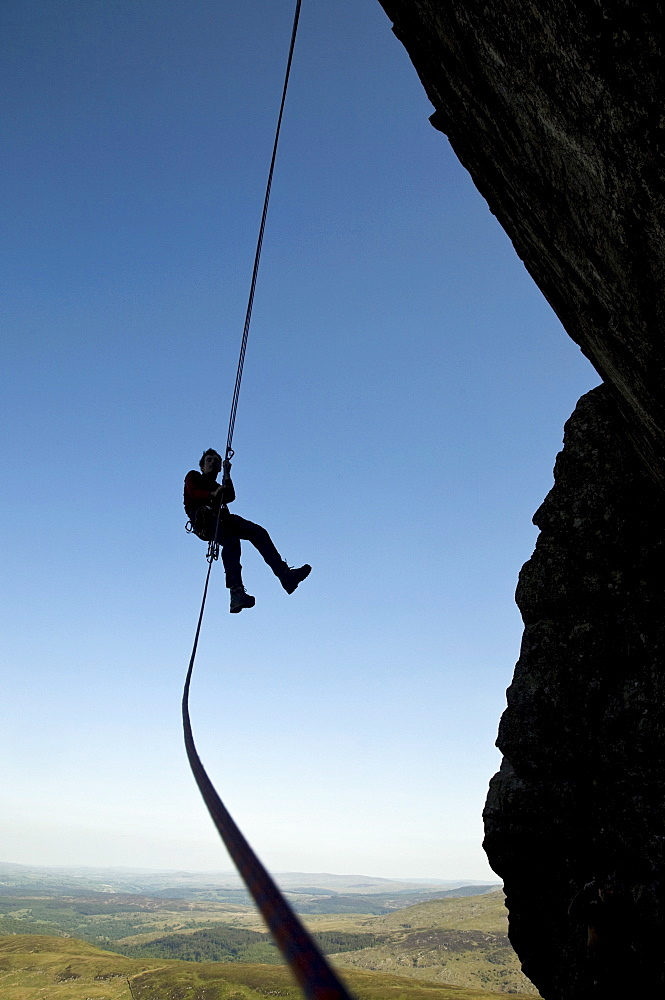 A climber makes a free-hanging abseil from a steep cliff in the Ogwen Valley, near Tryfan and Snowdon, Snowdonia, Wales, United Kingdom, Europe