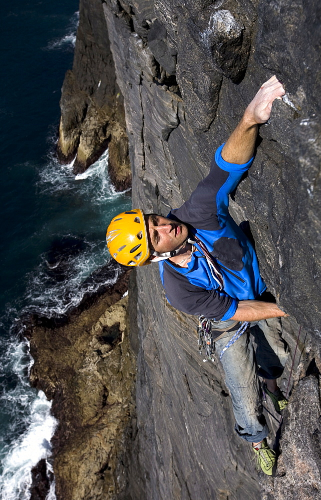 A climber makes his way up the huge vertical sea cliff on the west face of Dun Mingulay, Mingulay Island, near Barra and Lewis, Outer Hebrides, Scotland, United Kingdom, Europe