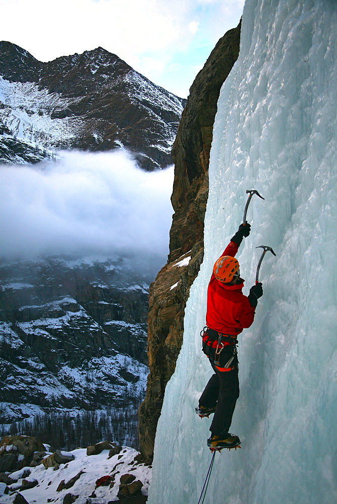 An ice climber makes his way up a frozen waterfall near Cogne, above the Aosta Valley, northern Italy, Europe