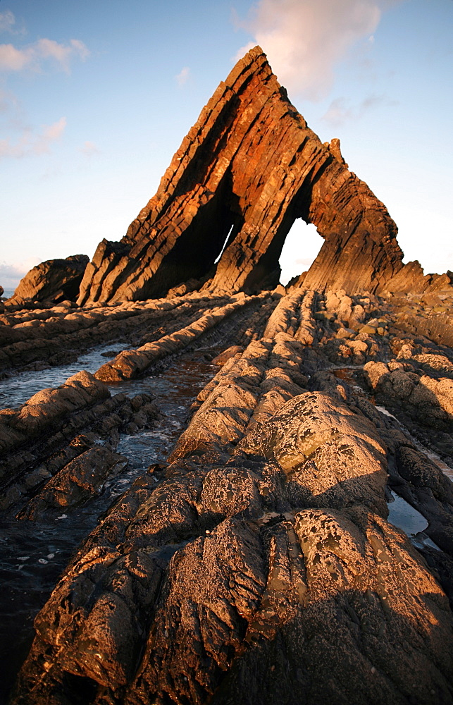The light of the setting sun illuminates the unusual architecture of Blackchurch Rock, which lies under cliffs between Clovelly and Hartland Point, Culm Coast, North Devon, England, United Kingdom, Europe