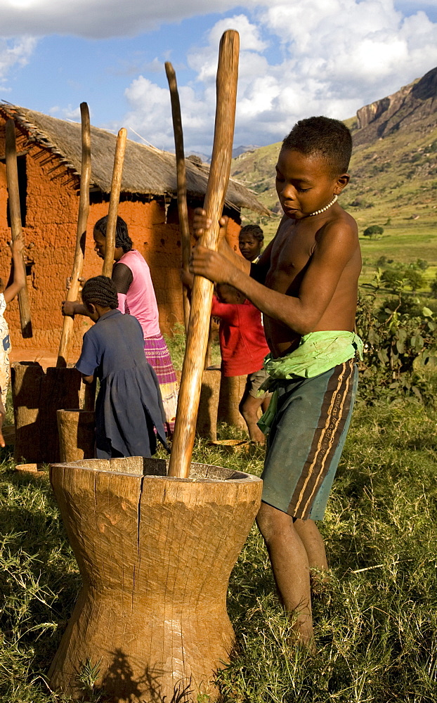 A local boy grinds millet by hand using a huge mortar and pestle, Tsaranoro Velley, Andringitra National Park, near the provincial city of Fianarantsoa, southern Madagsacar, Africa