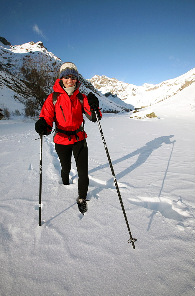 A trekker heads up into the wilderness of the highest part of the Ecrins Massif in deep winter snow, above the village of Pelvoux, near Briancon, western Alps, Hautes Alpes, south west France, Europe