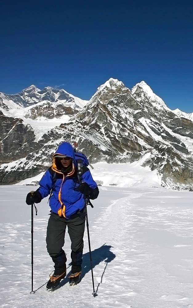 A climber walks towards advanced base camp at 5800 metres on Mera Peak, 6420 metres, a popular trekking peak in the Khumbu region, with Mount Everest beyond, Nepal Himalaya, Nepal, Asia