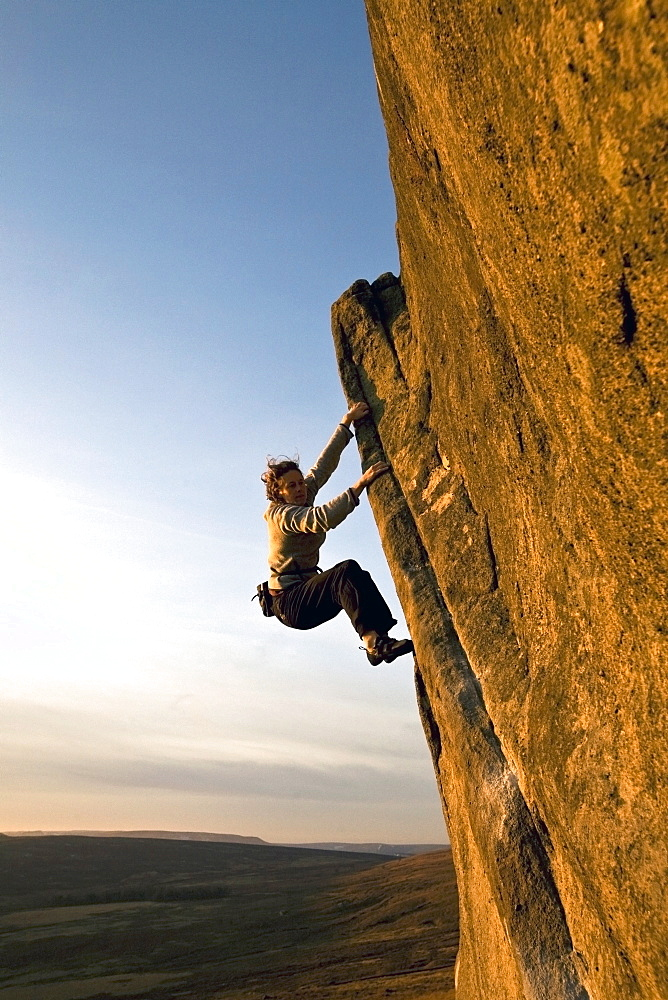A climber on a popular gritstone bouldering route on the Plantation Boulders at Stanage Edge, Peak District National Park, near Hathersage, Derbyshire, England, United Kingdom, Europe