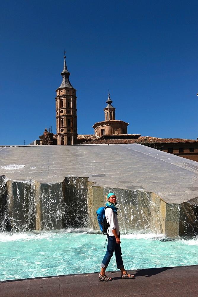 Woman beside water features of Plaza del Pilar, overlooking the Basilica de Nuestra Senora del Pilar, Zaragoza, Aragon, Spain