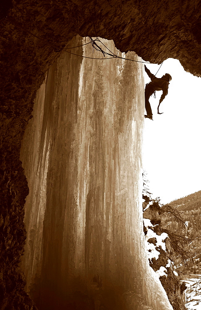 An ice climber scales a giant icicle in the valley of Crevoux, near Gap and Briancon, Ecrins Massif, western Alps, France
