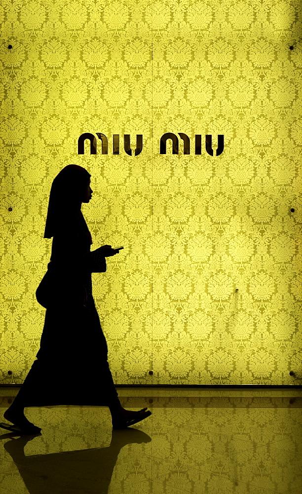 Muslim woman walking in front of the fashion store Miu Miu, Kuala Lumpur, Malaysia, Southeast Asia, Asia - 803-254