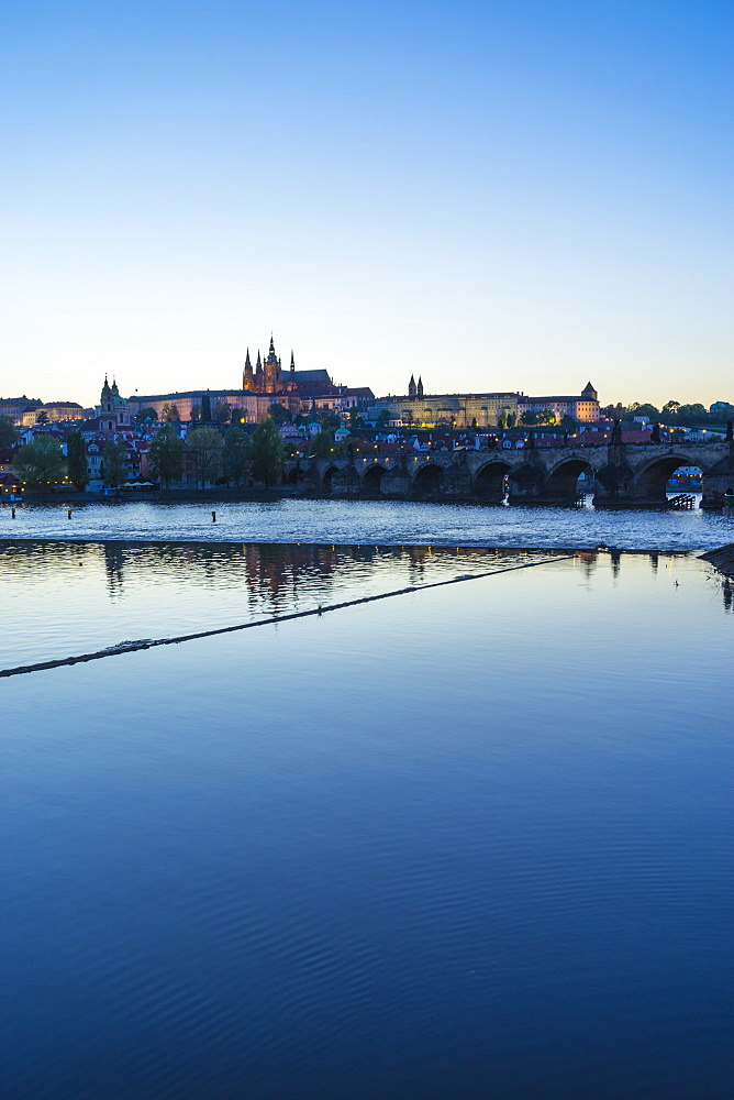 View of Charles Bridge, the Castle District and St. Vitus's Cathedral across the Vltava River at sunset, Prague, Czech Republic, Europe