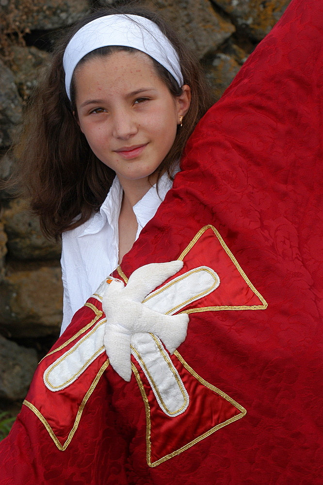 Girl carrying a banner in a Catholic procession during Espiritu Santo Festival in Vila Novo, Terceira, Vila Nova, Azores, Portugal, Europe