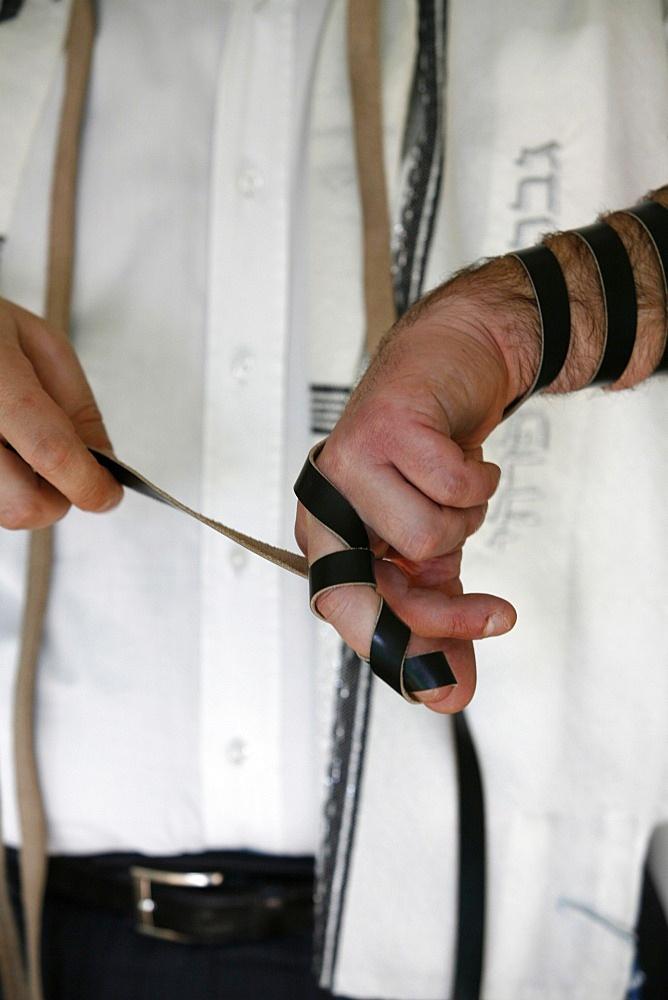 Rabbi putting on phylacteries, Paris, France, Europe