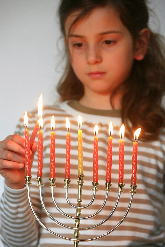 Girl lighting Hannuka candles, Montrouge, France, Europe