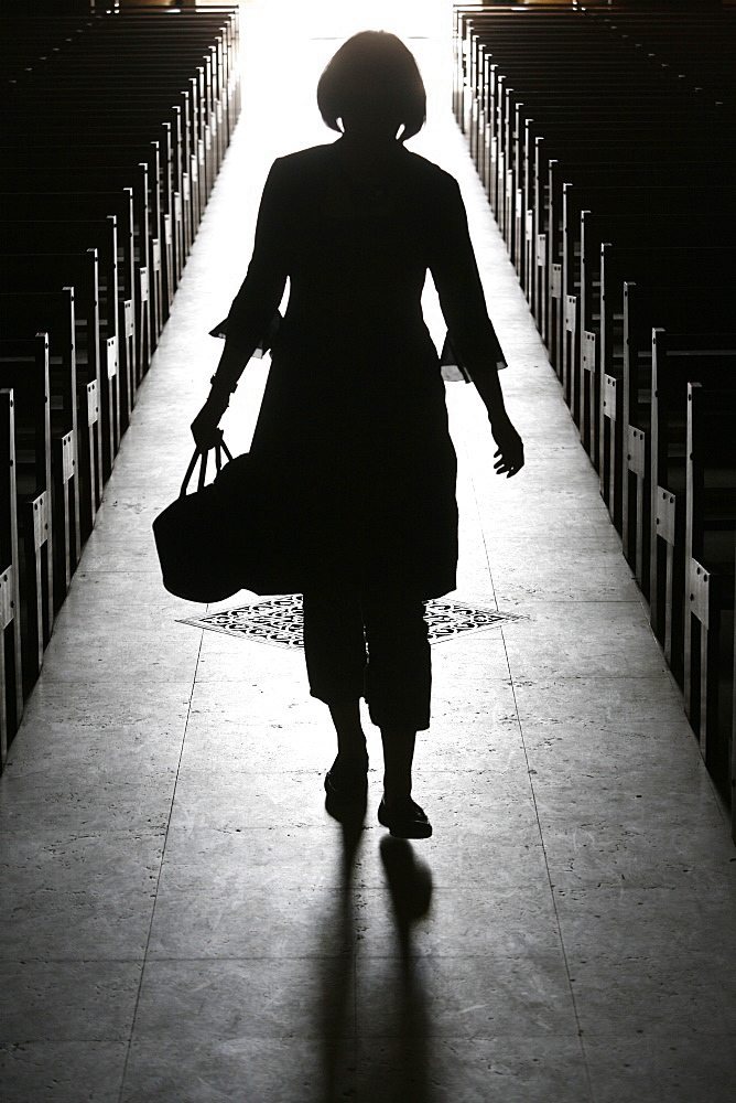 Silhouette of a woman in church