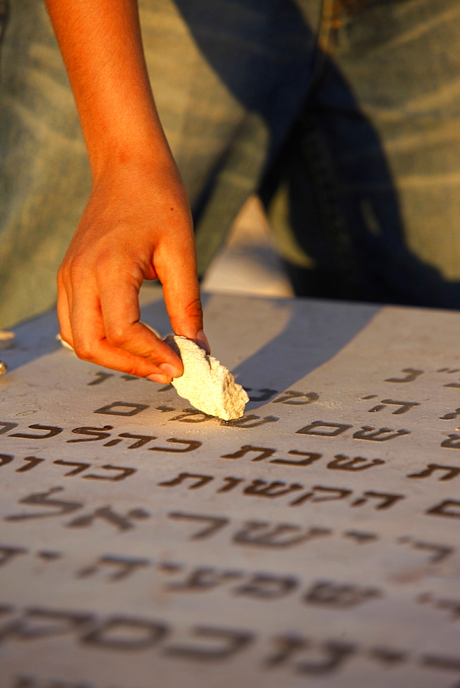 Boy placing stone on a grave in the Mount of Olives Jewish cemetery, Jerusalem, Israel, Middle East