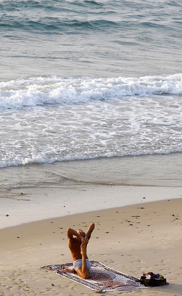 Man doing yoga on Jaffa beach, Jaffa, Israel, Middle East