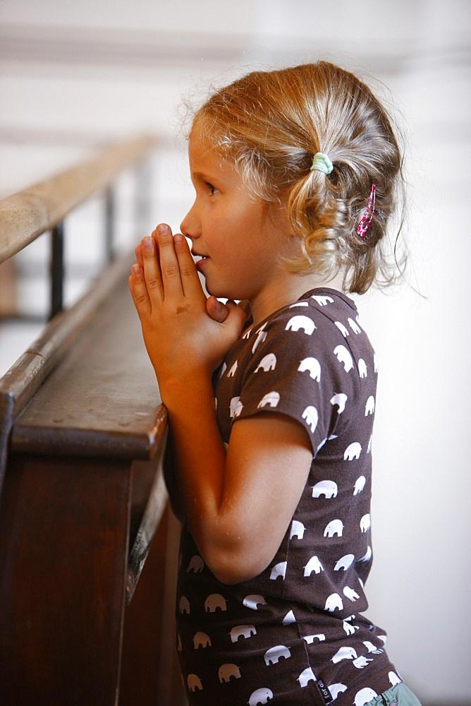 Girl praying in church, Saint Nicolas de Veroce, Haute Savoie, France, Europe