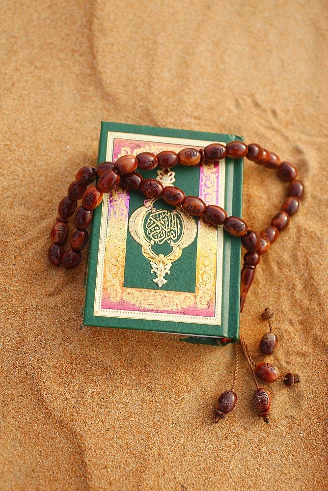 Koran and prayer beads in sand, Dubai, United Arab Emirates, Middle East