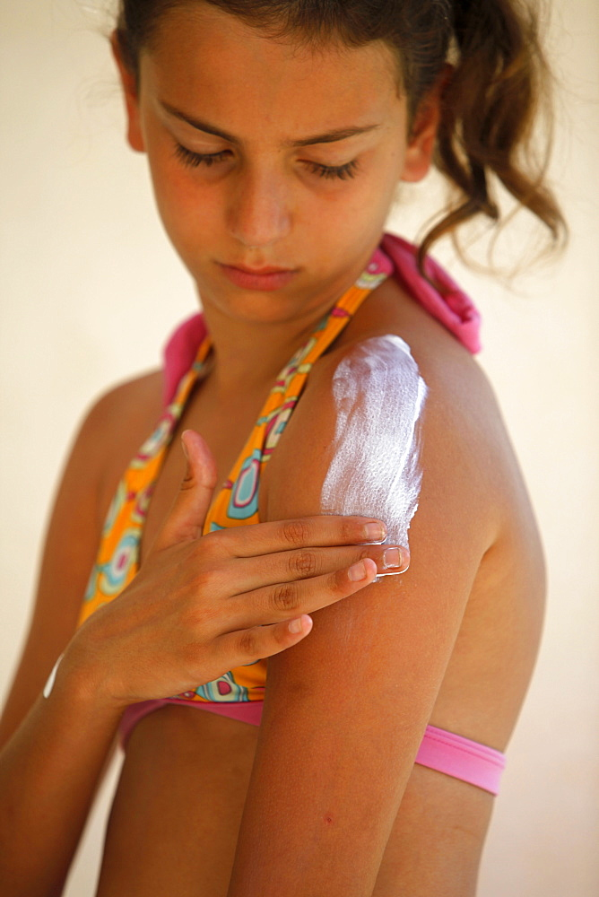 Girl putting on sunblock, Italy, Europe
