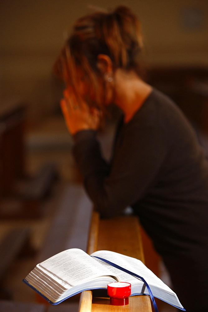 Candle and Bible, with woman praying in the background, Saint Nicolas de Veroce, Haute Savoie, France, Europe