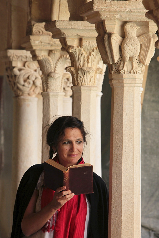 Woman reading the Bible in the Cloister of Saint Sauveur, Aix en Provence, Bouches du Rhone, Provence, France, Europe