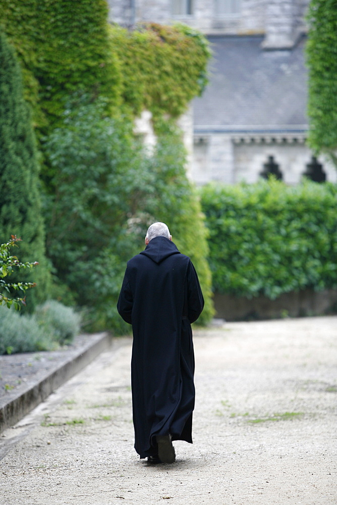 Monk walking in Saint-Pierre de Solesmes Abbey, Solesmes, Sarthe, Pays de la Loire, France, Europe