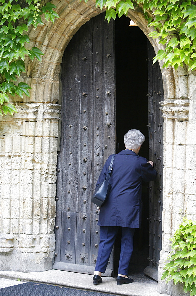 Woman walking into Saint-Pierre de Solesmes Abbey church, Solesmes, Sarthe, Pays de la Loire, France, Europe