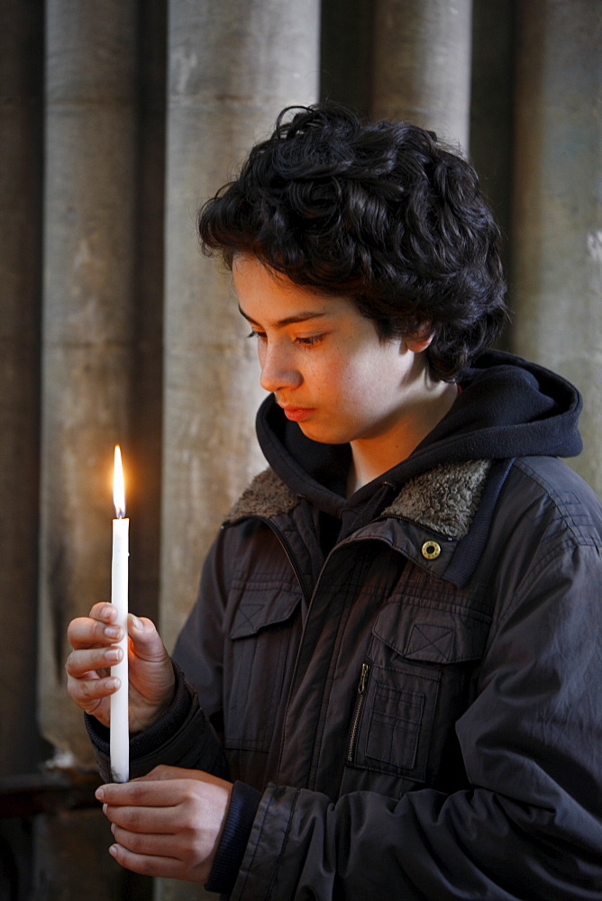 Teenager holding a candle in Notre Dame de Bayeux cathedral, Bayeux, Normandy, France, Europe