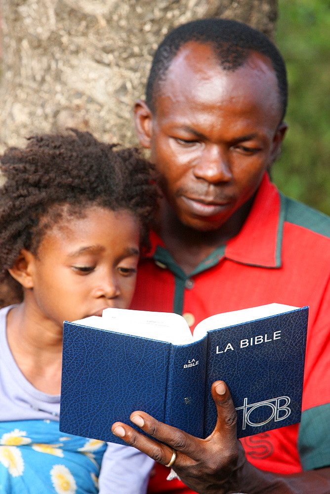 Father and daughter reading the Bible, Lome, Togo, West Africa, Africa
