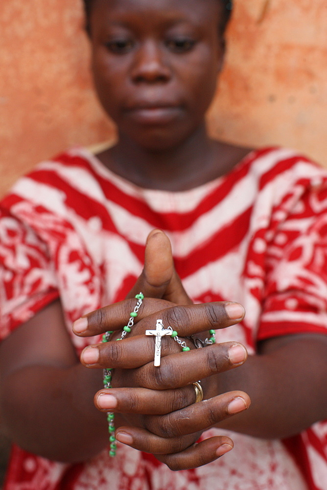 African woman praying the rosary, Lome, Togo, West Africa, Africa