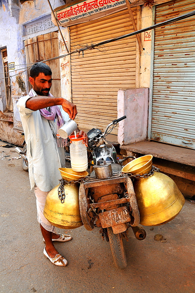 Milk collector carrying milk-churns on his motorbike, Pushkar, Rajasthan, India, Asia