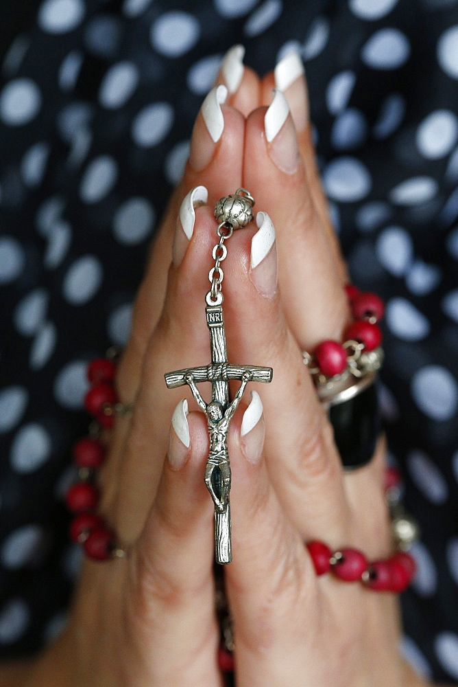 Woman praying with rosary, Paris, France, Europe
