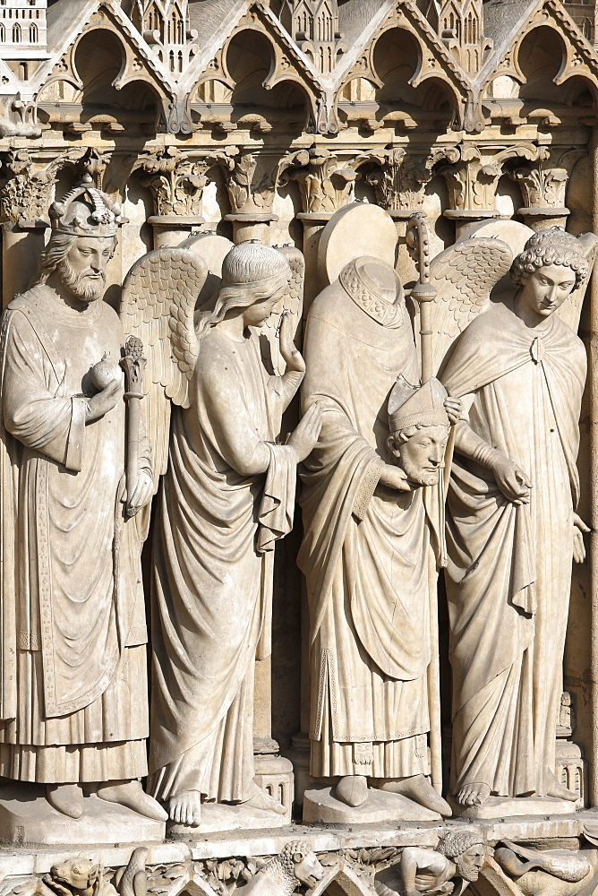 Detail of St. Denis holding his head flanked by two angels, Virgin portal, Western facade, Notre Dame de Paris Cathedral, Paris, France, Europe