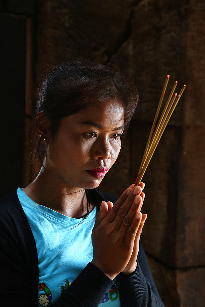Khmer woman praying in a temple. Cambodia.