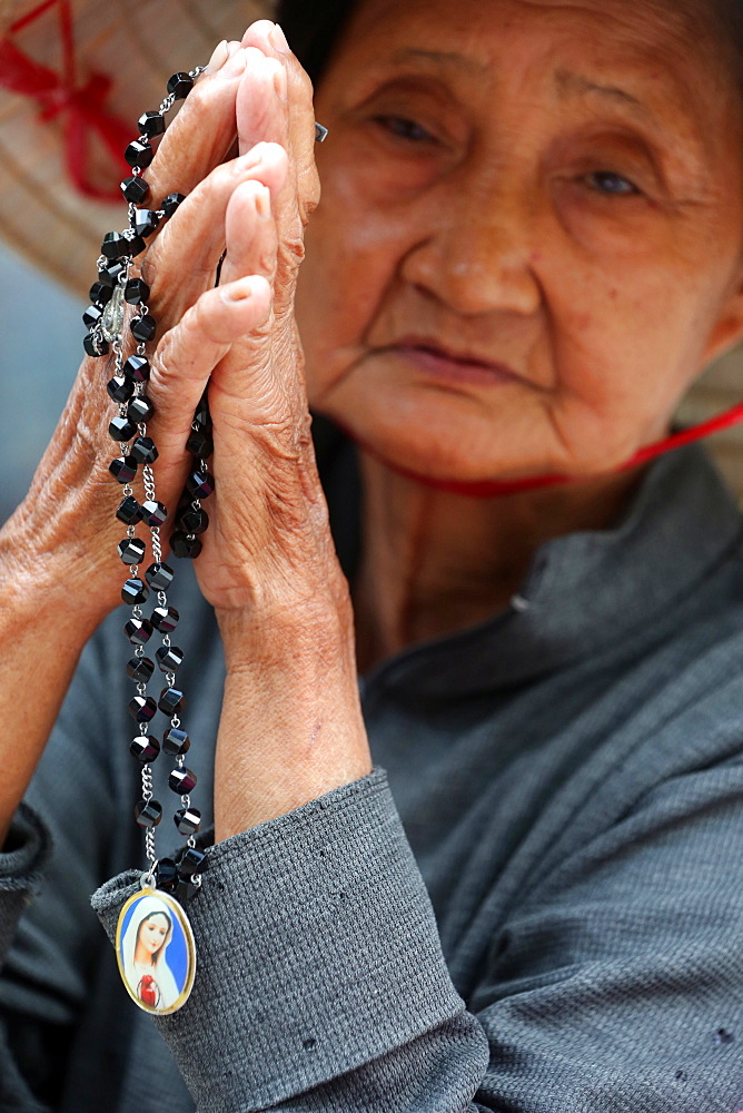 Old Vietnamese woman praying with prayer beads, St. Philip Church (Huyen Sy Church), Ho Chi Minh City, Vietnam, Indochina, Southeast Asia, Asia