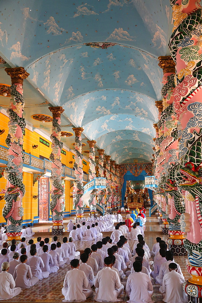 Cao Dai Holy See Temple. Praying devout men and women, ceremonial midday prayer. Thay Ninh. Vietnam.