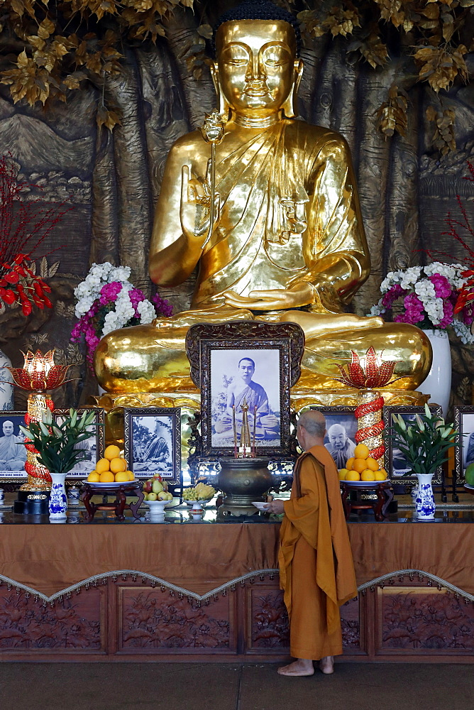 Minh Dang Quang buddhist temple. Golden Buddha with lotus flower and buddhist monk. Ho Chi Minh city. Vietnam.