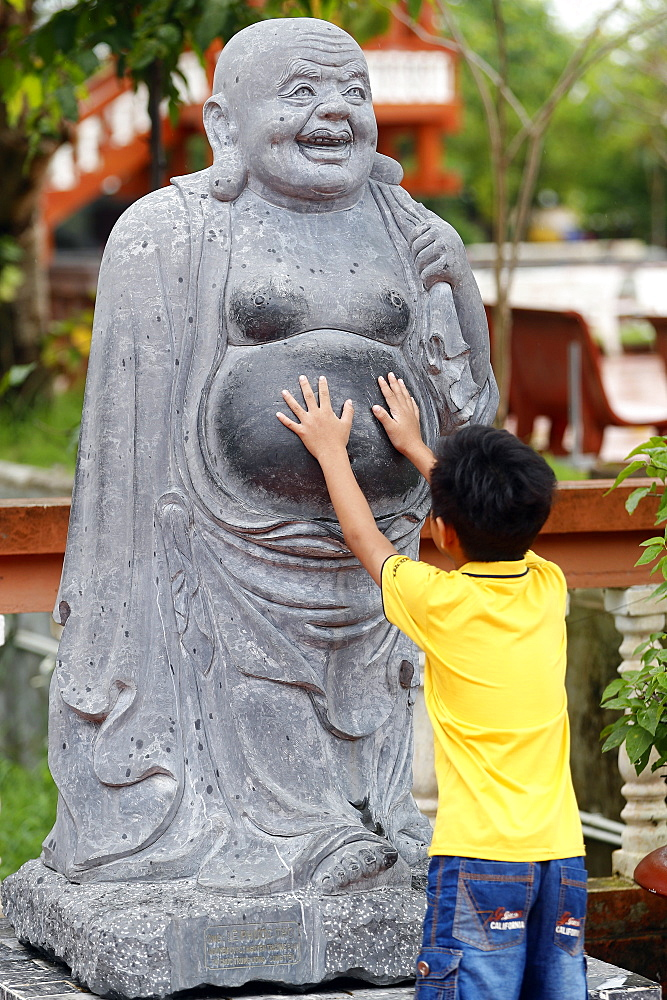 Truc Lam Phuong Nam Buddhist temple, small boy touching Angada statue, Can Tho, Vietnam, Indochina, Southeast Asia, Asia
