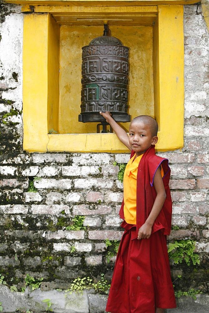 Young monk and prayer wheel, Swayambhunath temple, Kathmandu, Nepal, Asia