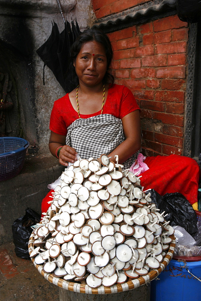 Woman selling butter lamps, Patan, Nepal, Asia