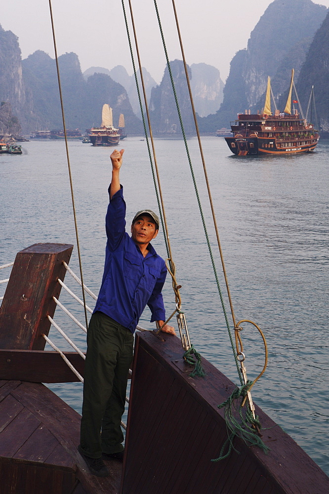 Crewman raises anchor on junk Ha Long Bay, Vietnam, Indochina, Southeast Asia, Asia - 812-107