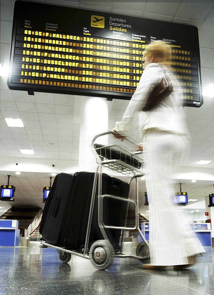 Woman with baggage trolley in departures, Ibiza Airport, Spain, Europe - 812-180