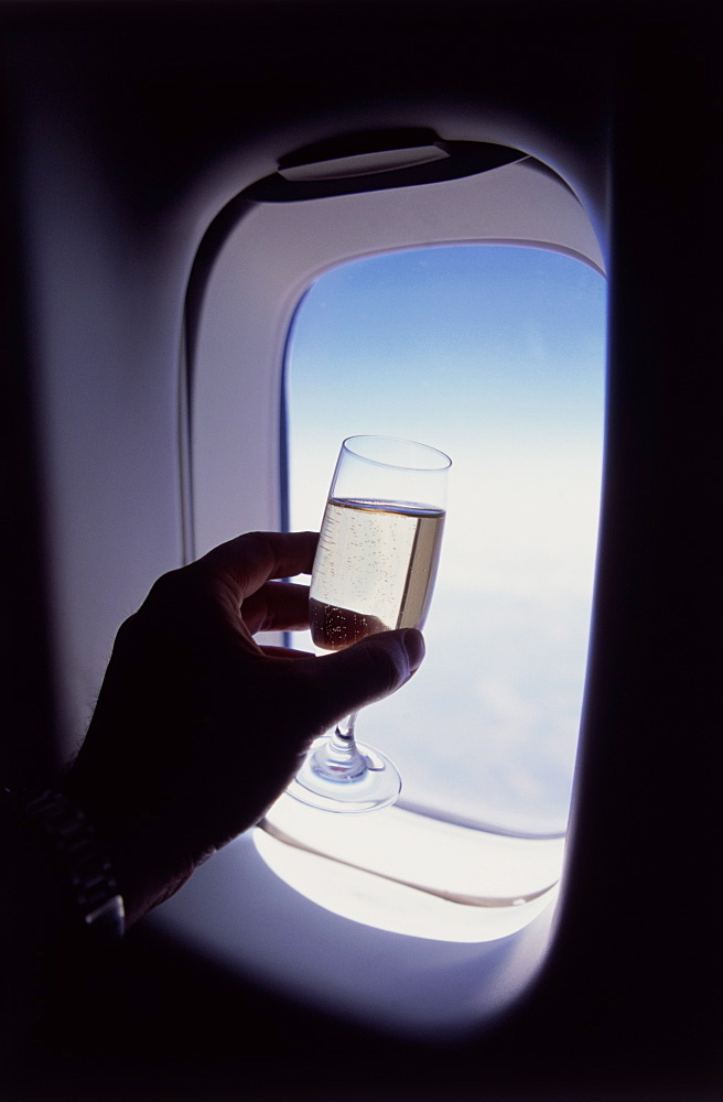 Glass of champagne at 30000 feet and aircraft window - 812-182