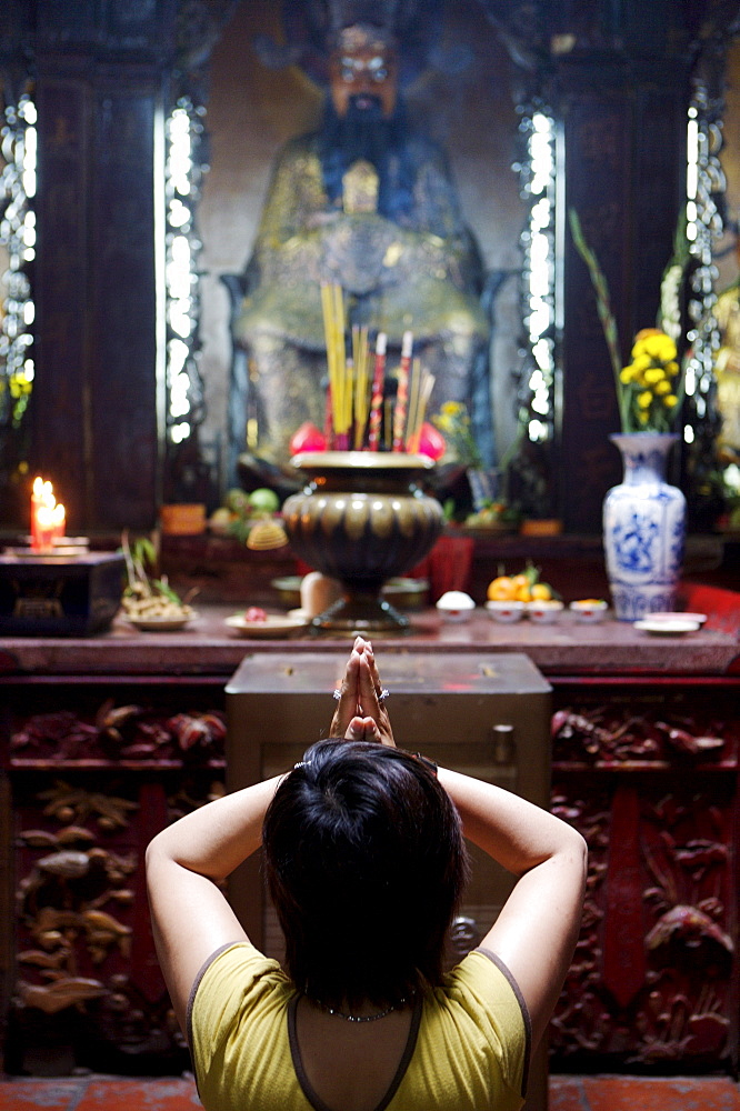 Local woman praying and meditating in front of offerings in Buddhist temple, Ho Chi Min City, Vietnam, Indochina, Southeast Asia, Asia