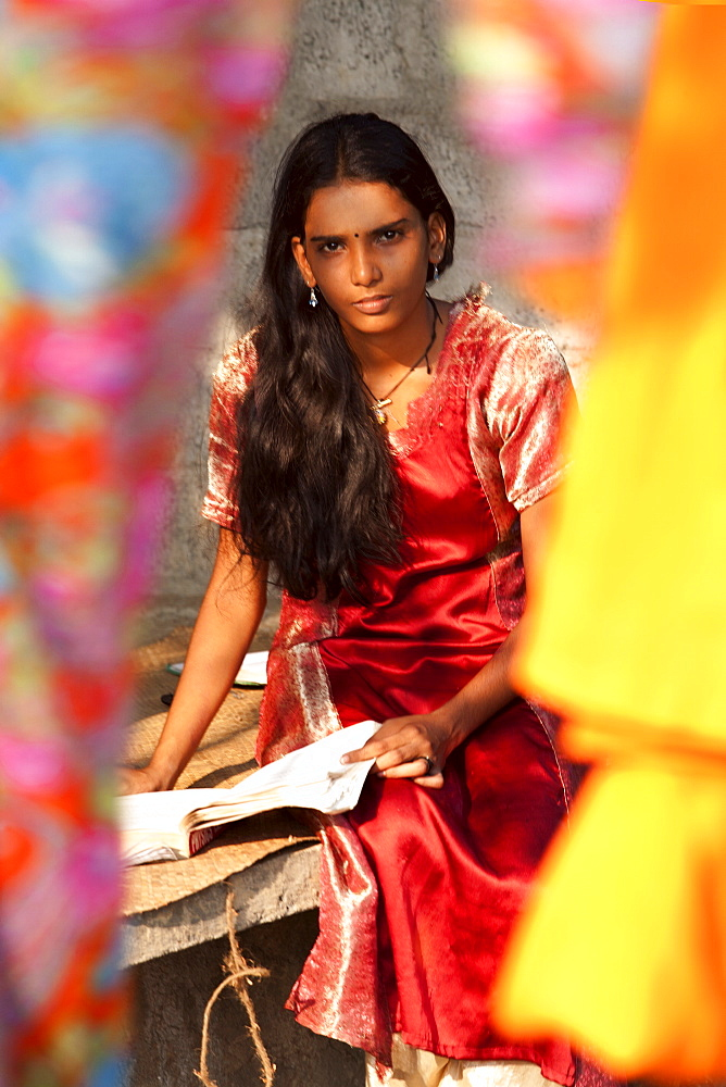 Student girl, sitting behind bright coloured silks, Kerala, India, Asia - 812-227